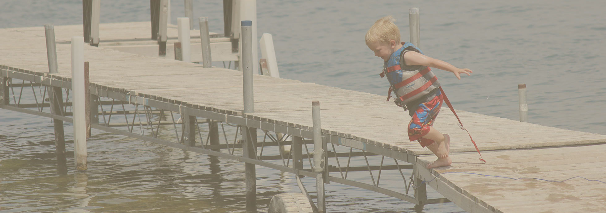 Happy young kid in life vest jumping into water from a boat dock at Eastbay Campground.