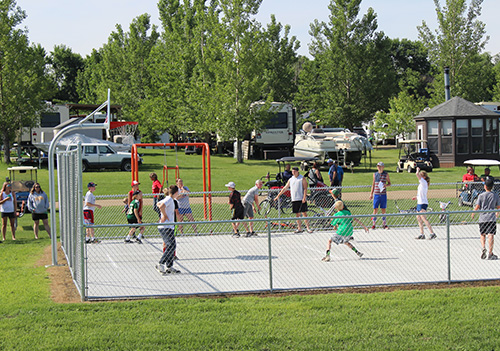 A group of kids, teens, and adults playing a game of basketball on the Eastbay Campground basketball court on a sunny day.